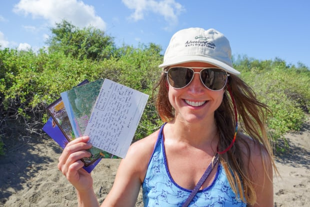 A young woman smiling and holding postcards in the Galapagos