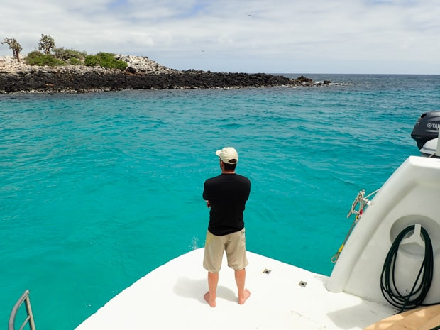 A man standing on the stern of a Galapagos small ship looking at the turquoise water and a nearby island