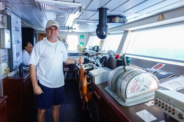 A Galapagos ship captain at the helm of a small ship