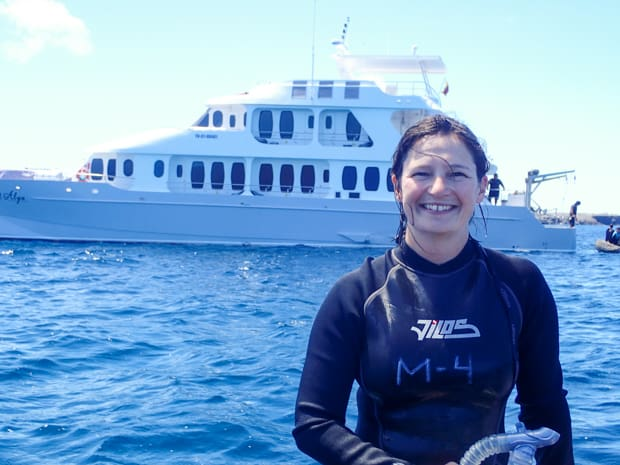 A woman in a wetsuit in front of a Galapagos small ship smiling after snorkeling