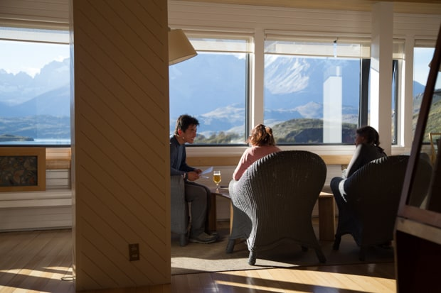 Travelers enjoying time in the Explora Lodge while enjoying the panoramic view of the mountains of Torres del Paine National Park.