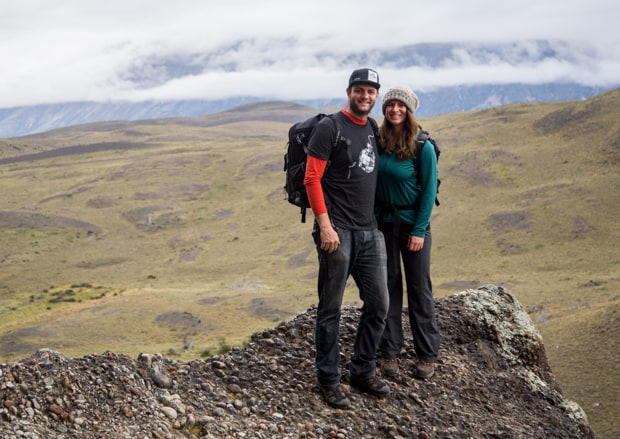 Happy couple on a rocky point overlooking the valley floor in Patagonia.