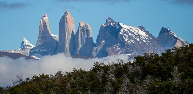 Landscape view of granite rock towers and mountains amongst the forest in Torres del Paine National Park on a Patogonia land tour.
