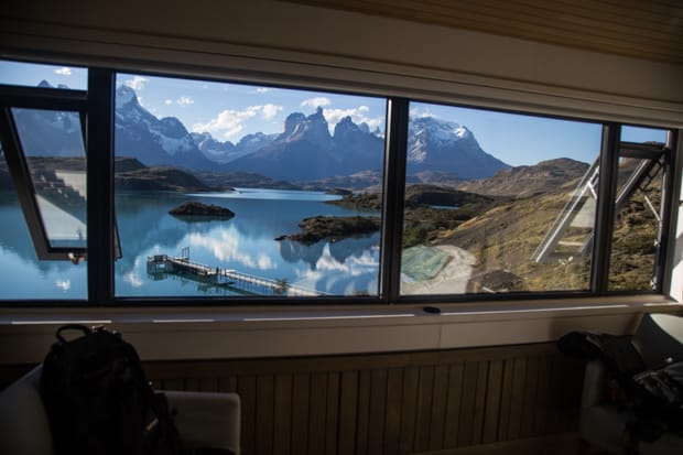 Panoramic view from a window at Explora Lodge of Lake Pehoe and snowcapped mountains in Patagonia's Torres del Paine National Park.