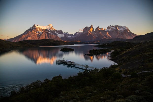 Bird's eye view of a sunset of Lake Pehoe and the mountain range reflecting in the lake at Torres del Paine National Park.