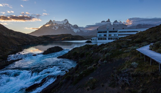 Explora Lodge set on a hillside next to the shore of Lake Pehoe on a Patagonia land tour with snow capped mountains in the background.