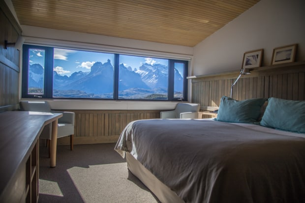 Explora Lodge view of a room with a bed, chairs, desk and a window with a panoramic view of mountains in Torres del Paine National Park land tour.