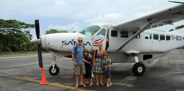 Family Travelers standing in front of a plane in Costa Rica