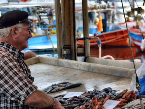 Local at the fish market with fishing boats in the background seen from a small ship excursion in Greece.