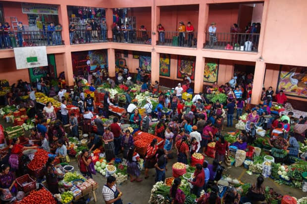 A local food market bustling with locals and a variety of fruits and vegetables in the courtyard of a building.