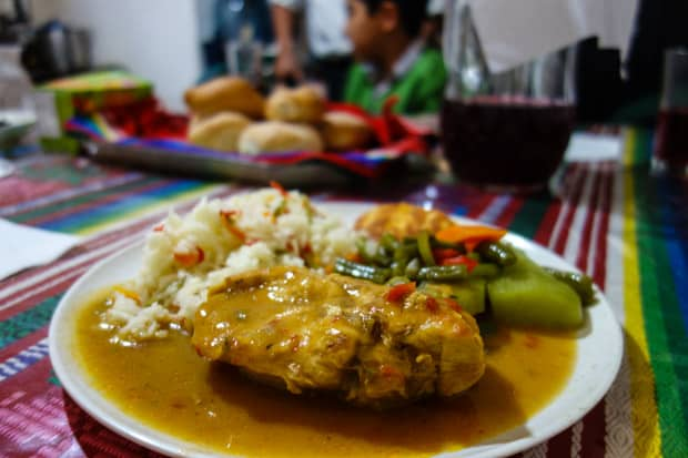 Plated Guatemalan food of rice, chicken and vegetables on a table with a colorful weaved table cloth.