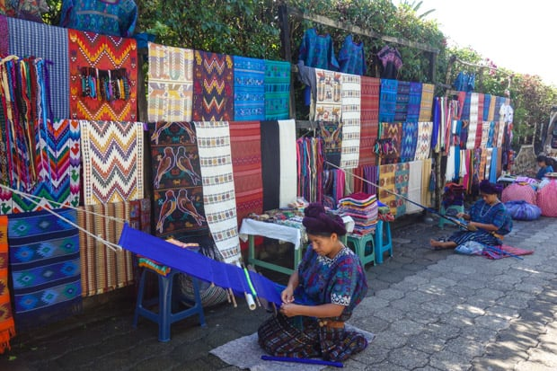 Street market with traditionally clad Guatemalan women weaving textiles and displaying a wide variety of colorful blankets.
