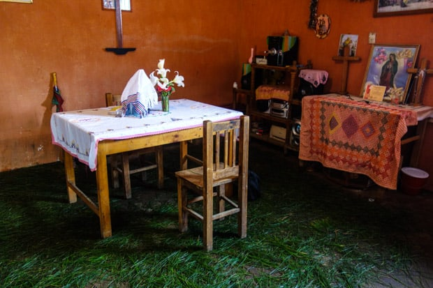 Local Guatemalan family home with grass laced on the floor dining table and chairs and religious catholic altar.