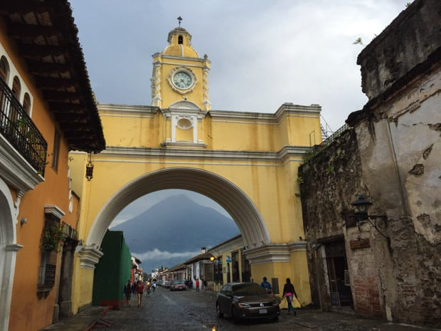 City of Antigua in Guatemala with yellow archway with clock in a steeple with a cross on a local street.