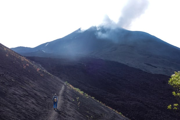 Guatemalan traveler hiking on a trail of a volcanic hillside with Volcan Agua smoking in the distance.