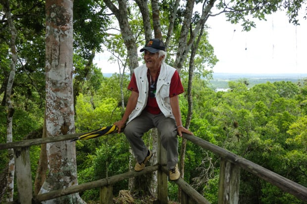 Guatemalan guide sitting on a wood railing in a rainforest in Yaxha.