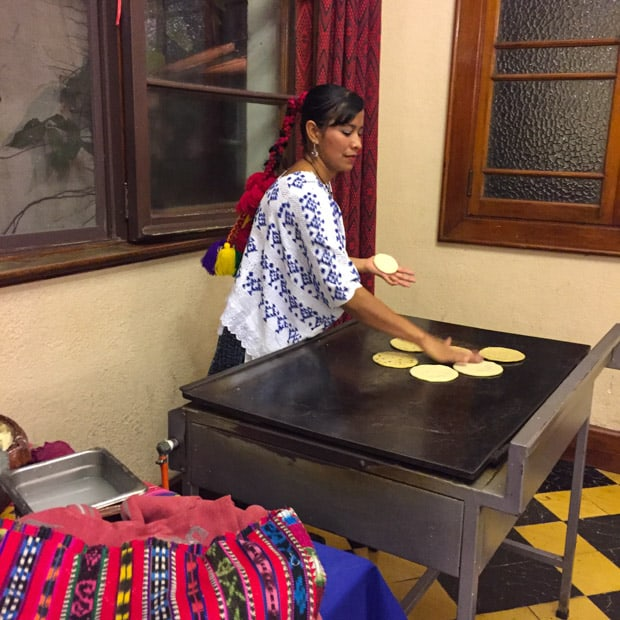 Guatemalan local woman heating up homemade tortillas in a kitchen.