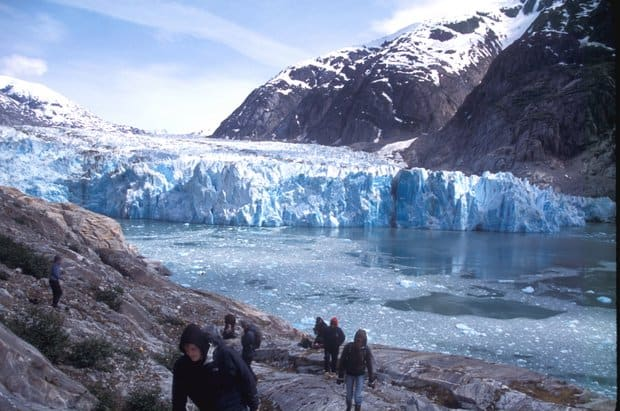 Alaskan travelers hiking on rocks in front of a tidewater glacier and iceberg bits.