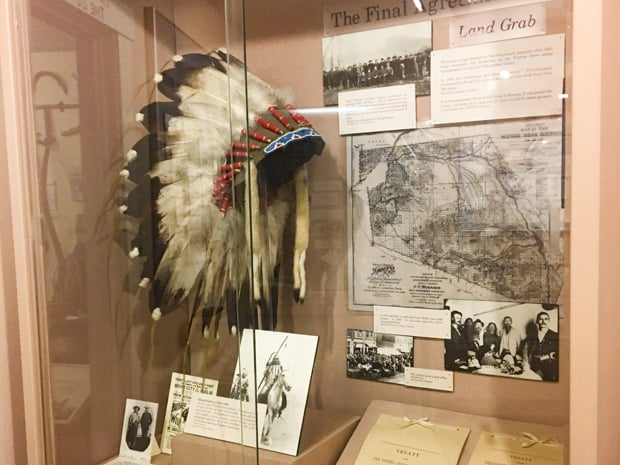 A glass showcase at the Nez Perce county Historical Society museum showing a native american headdress and old pictures.