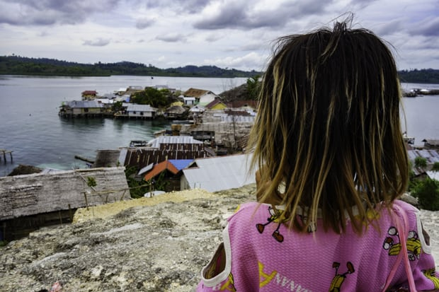 A young girl looking out over a coastal village in Indonesia.