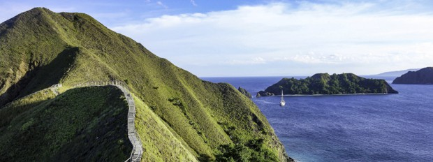 An Indonesian island peak with a stairway hiking trail along the ridge and a small ship anchored off the coast line.