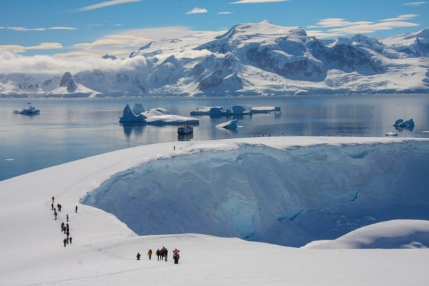 People snowshoeing uphill on Antarctica with their small cruise ship in the background.