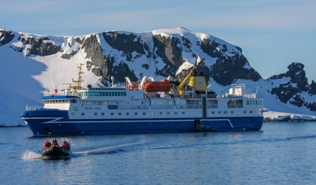 Small ship in Antarctica with a skiff full of guests leaving.