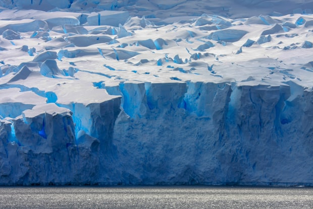 Shades of blue and white on a large ice shelf in Antarctica seen from a small ship.