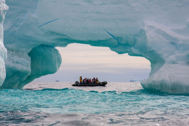 Guest from a small ship on a skiff under the arch of an iceberg.