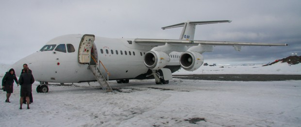 People getting on a plane on the snow in Antarctica.