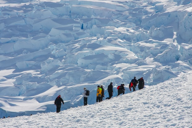 Guests from a small ship on a hiking excursion in Antarctica with only white snow formations in the background.
