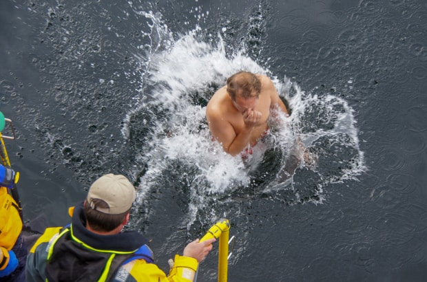 Man jumping into the water in Antarctica from his small ship during  a polar plunge event.