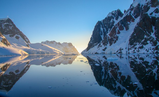 Reflection of mountains in a calm channel seen from a small ship cruise in Antarctica.