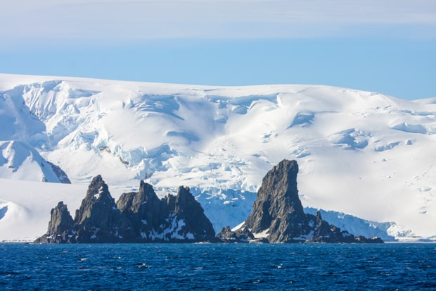 Landscape of jagged rocks and white hills in Antarctica seen from a small ship cruise.
