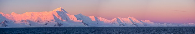 Sunset turning the mountains pink in Antarctica seen from a small ship cruise.