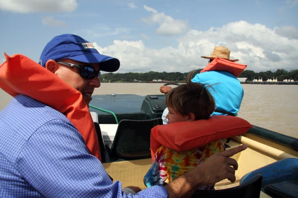 2 travelers and a guide cruising in a small boat in the Panama canal zone.