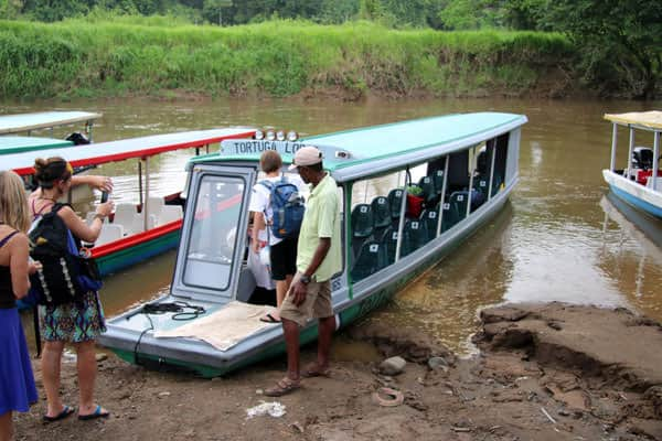Families of travelers embarking on a covered open air boat on a river in Costa Rica.