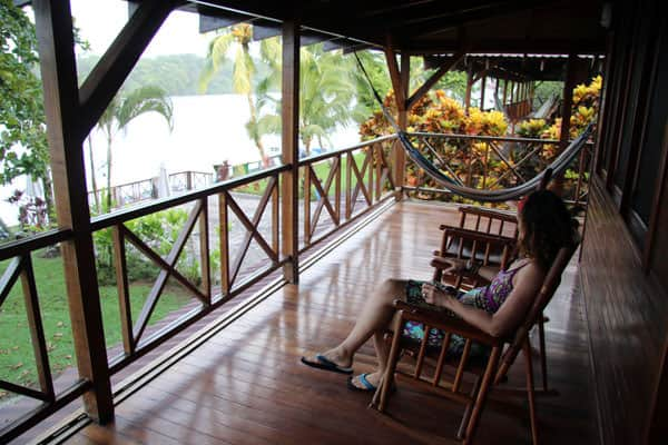 Traveler in Costa Rica rocking on a chair on the deck overlooking the river and garden.