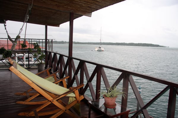Bocas Inn view from the open air deck facing the ocean with a catamaran in the distance.