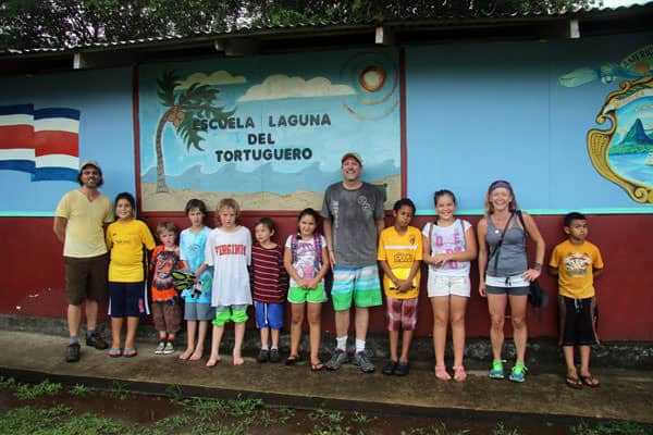 Families of travelers and local community kids posing in front of a school.