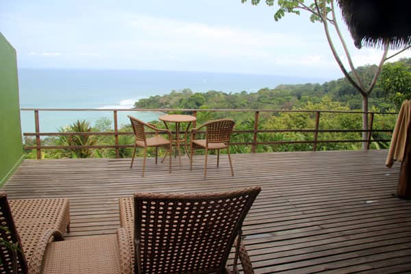 View of a deck with chairs and tables located atop the Costa Rican rainforest and the ocean.