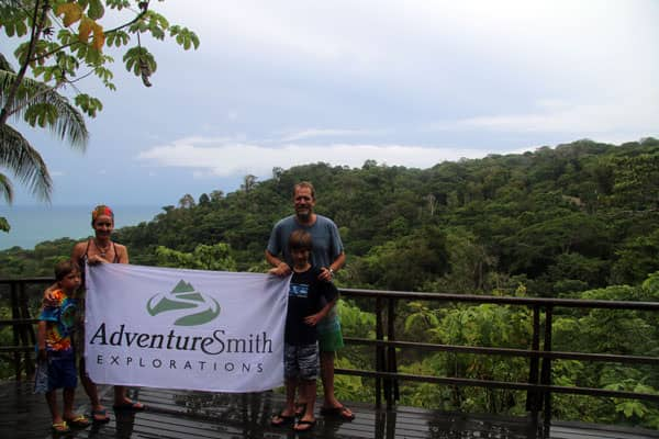 Family of travelers in Costa Rica holding a Adventuresmith Explorations flag on a deck in the rainforest with the ocean in the background.
