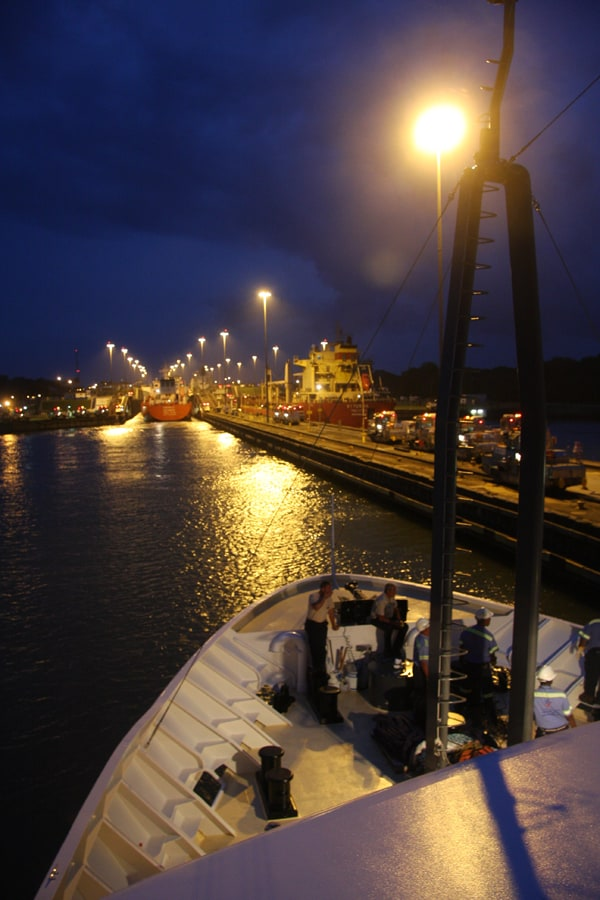 Bow of a small ship cruise going through locks in the Panama canal in the evening.
