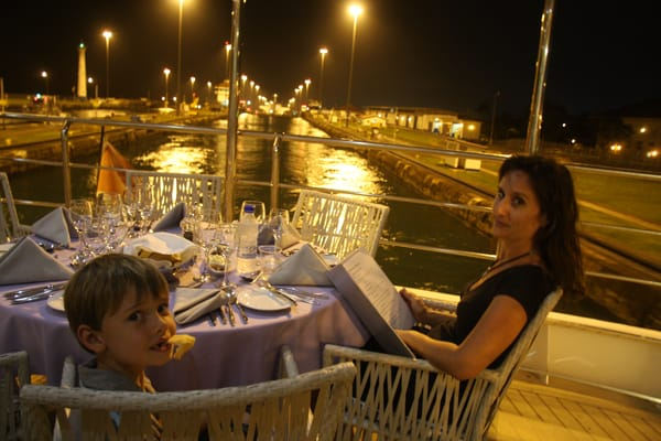 Family having dinner on the outside deck of their small ship cruising through the locks in the Panama Canal.