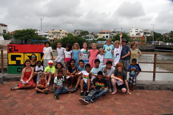 Group of local and young Galapagos travelers posing together on a sidewalk of a small Galapagos town.