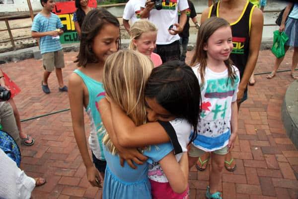 Local Galapagos girl and young Galapagos traveler hug with other kids around.