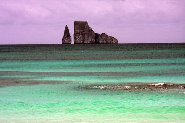 Sunset view from the beach of granite spire and rock formations in the ocean with green ocean water on the shoreline in the Galapagos.
