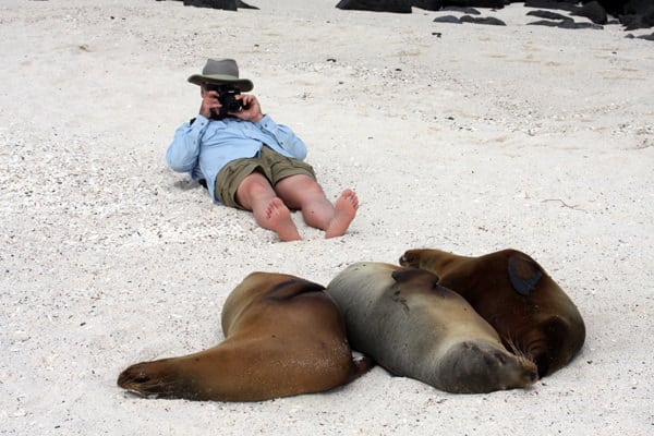 Galapagos traveler laying on his back photographing 3 sleeping sea lions on a beach.