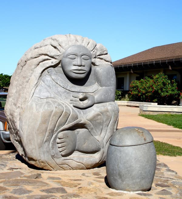 Hawaiian Hina statue carved into a large gray rock. Depicting a woman with long hair and eyes closed