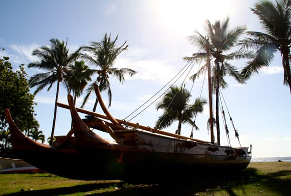 Hawaiian double-hulled canoe pulled up onto the beach